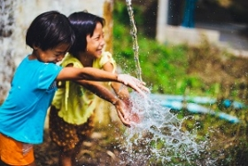 Two girls splashing water in their hands.